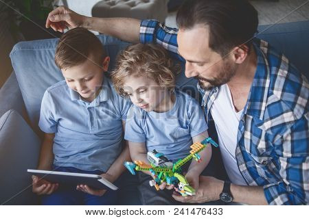 Top View Concentrated Kids And Focused Adult Looking At Digital Device In Room
