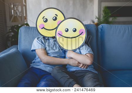 Outgoing Children With Cartoons Faces Situating On Comfortable Sofa While Looking At Camera