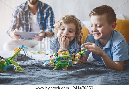 Portrait Of Cheerful Kids Playing With Robot. Dad Looking At Digital Device
