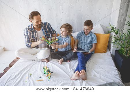 Full Length Portrait Of Happy Parent Having Good Time With Satisfied Children While Situating In Bed
