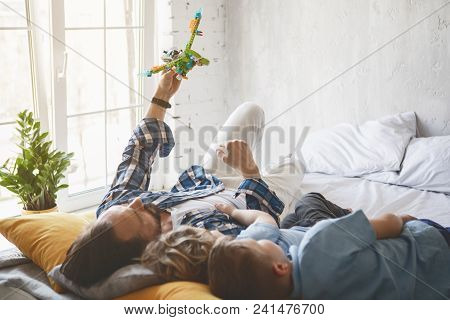 Smiling Farther Playing With Children With Toys. They Resting On Bed. Glad Parent Having Fun With So