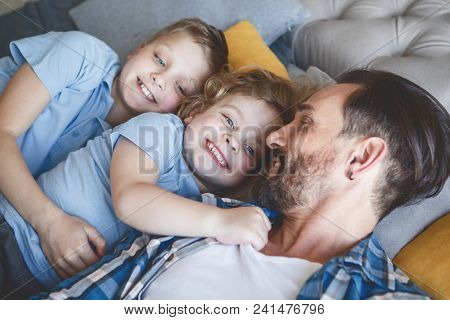 Outgoing Little Children Embracing Satisfied Dad While Resting Together. Positive Family Concept