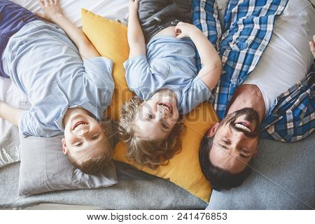 Top View Portrait Of Satisfied Sons Relaxing On Pillows Near Outgoing Father. Happy Family Concept
