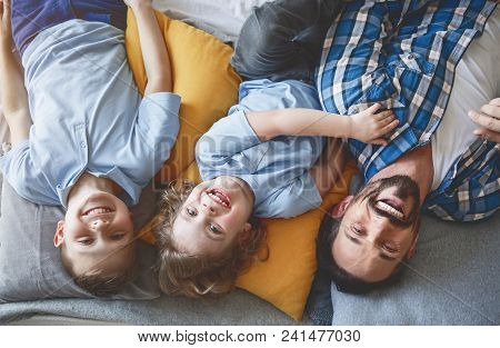 Portrait Of Cheerful Bearded Father Relaxing On Pillows With Two Little Smiling Kids. They Looking A