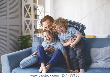 Portrait Of Laughing Dad Hugging Beaming Kids Having Entertainment On Sofa In Living Room. Satisfied