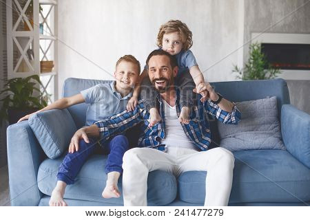 Portrait Of Cheerful Father Having Fun With Two Outgoing Children While Sitting On Sofa. Glad Parent