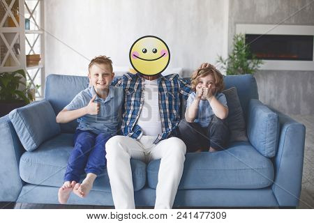 Portrait Of Outgoing Children With Positive Parent Having Fun On Couch In Living Room. Happy Parent