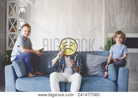 Portrait Of Smiling Brothers And Sad Dad With Emoji Appearance Sitting On Sofa In Living Room. Kids