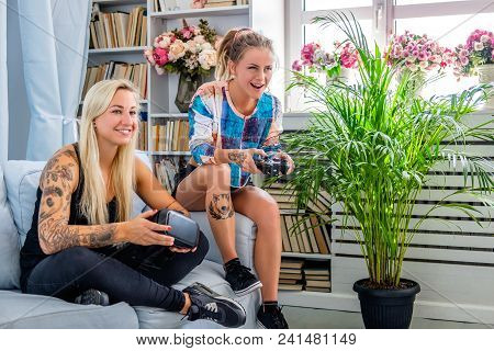 Two Sexy Females Having Fun With Virtual Reality Glasses Device At Home.