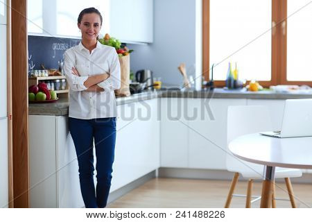 Portrait of young woman standing with arms crossed against kitchen background. Woman in the kitchen.