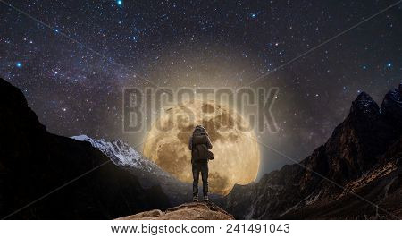 A Man With Backpack Standing On Mountain Peak At Night, And Silhouette Mountain With Bright Full Moo