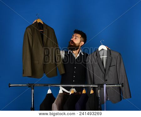 Designer Makes Choice Near Clothes Hangers. Tailoring And Design Concept. Tailor With Curious Face H
