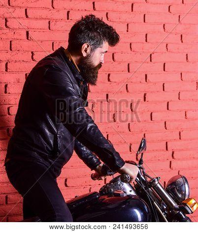 Man With Beard, Biker In Leather Jacket Near Motor Bike In Garage, Brick Wall Background. Start Of J