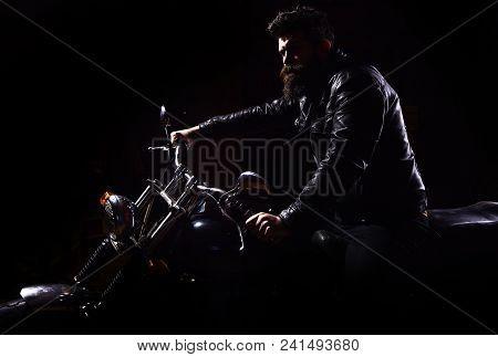 Man With Beard, Biker In Leather Jacket Sitting On Motor Bike In Darkness, Black Background. Night R