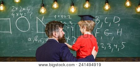 Best Friends Concept. Child In Graduate Cap Listening Teacher, Chalkboard On Background, Rear View.