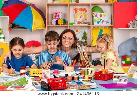 Painting projects for kids in playroom organization of children painting and drawing in kid's club. Craft lesson in primary school. Kindergarten teacher and students work together. Features of working