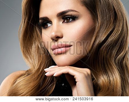Closeup portrait with a pretty female face. Beautiful young woman with long brown hair.  Fashion model with plump lips  posing at studio.
