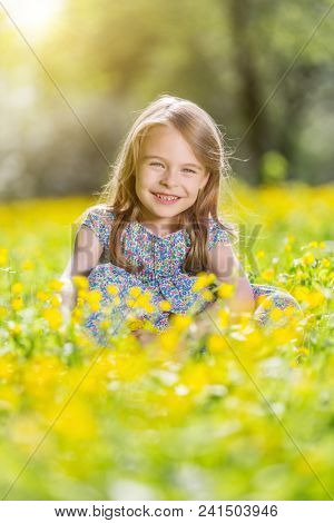 Happy little girl on spring blooming meadow