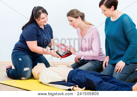 First aid trainees learning to use defibrillator for reanimation in first aid course