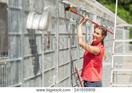 Zookeeper woman working on cleaning cage in animal shelter with sweep