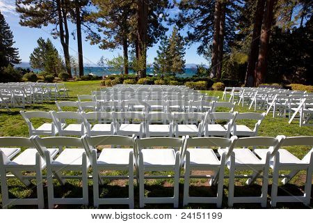 White Event Chairs In Scenic Garden By A Lake