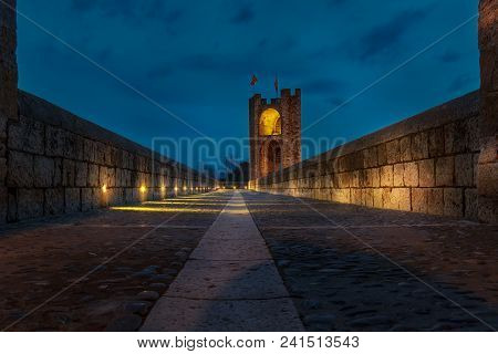 Middle age bridge of Besalъ enlightened at night under a partial cloudy blue sky poster