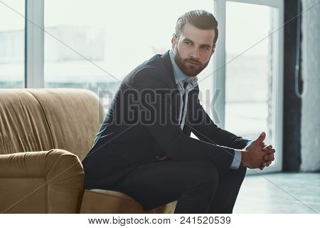 Young Bearded Stylish Businessman Leader Indoors At Office Sitting Looking Aside Holding Sunglasses