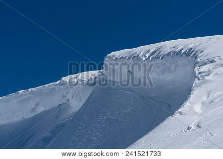 Mountain Ridge Covered By Snow Packed By The Wind On Sunny Bluebird Day
