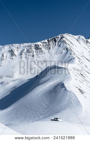 Two Skiers Leaving Mountain Hut Partly Covered By Snow At Bottom Of Mountain Ridge And Summit On Blu