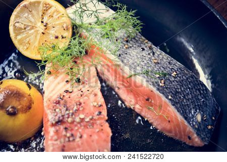 Grilled salmon fillet being sprinkled with salt and pepper