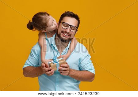Happy Father's Day! Cute Dad And Daughter Hugging On Yellow Background.