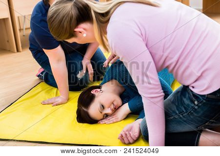 Women in first aid course training to position injured person