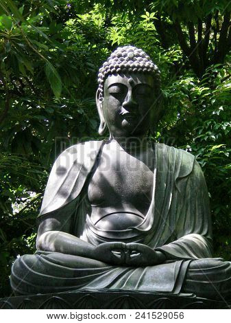 A Sitting Buddha Statue Rests Against A Backdrop Of Green Trees And Bushes. The Statue Is Grey Stone