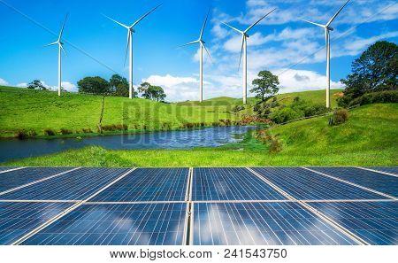 Solar Panel And Wind Turbines Farm On Green Hills.