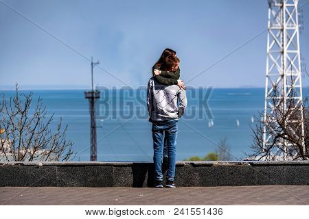 Romantic Picture Of Young Man And Woman Hugging Each Other With Sea Poet In Background