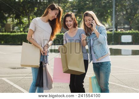 Group Of Young Asian Woman Shopping In An Outdoor Market With Shopping Bags In Their Hands. Young Wo