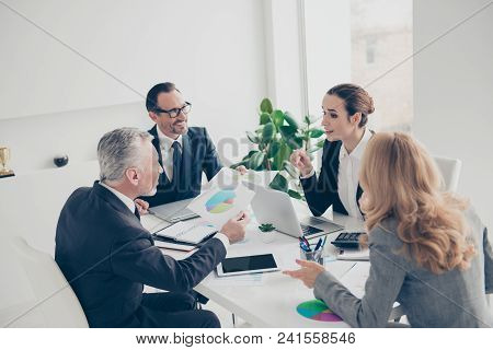 Four Stylish, Attractive Business Persons Sitting At Desktop In Work Place, Station, Using Laptops,