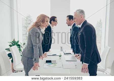 Business Competition, Four Stylish Business Persons In Suits Having Disagreement And Conflict, Stand