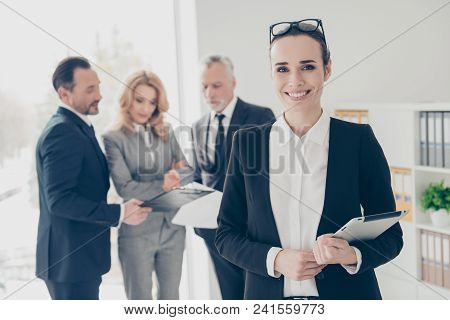 Smiling, brunet, cheerful director in formal wear holding gadget in hands, having glasses on her head, her colleagues on blurred background discuss project, standing on work place, station poster