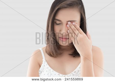 Asian Woman Suffering From Strong Eye Pain Against Gray Background. Female Has A Pain In The Eye. He