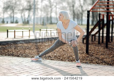 I Love Sport. Serious Aged Woman Wearing Sports Clothes And Exercising In The Open Air