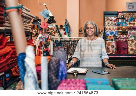 Portrait Of A Smiling Mature Fabric Shop Owner Standing Behind The Counter Of Her Fabric Shop Surrou