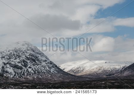 Snowcapped Mountains In Scottish Highlands Near Glencoe, Scotland, On A Foggy Spring Day.