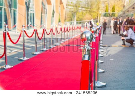 Close Up Red Carpet Ceremony With Selective Focus On The Stanchions And The Ropes With Blurred Guest