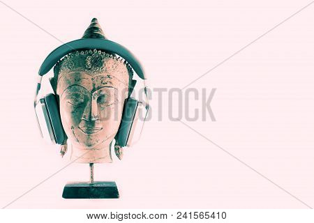 Spiritual Music Therapy. Buddha Head In Meditation With Modern Headphones. Representation Of Mindful