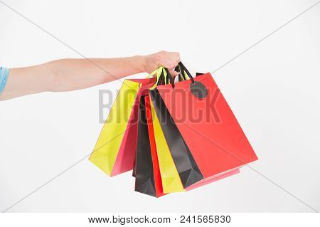 Shopping Bags In Hand. Paper Bags Of Different Colors. Bags Or Paperbags Isolated On White. Shopping