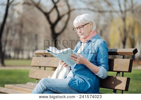 Avid Reader. Involved Blond Woman Reading A Book While Sitting On The Bench