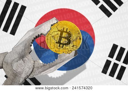 Bitcoin (btc) Coin In A Vice Under Pressure On South Korea (rok) Flag Background. Prohibition Of Bit
