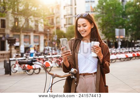 Image of young woman outdoors with bicycle on the street looking aside chatting by mobile phone drinking coffee.