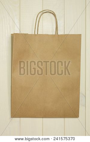 Paper Shopping Bag On A Wooden Background. Bag Template For Design With Copy Space. Empty Brown Bag